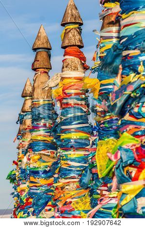 Buddhism symbol - ritual shaman pillars Serge with colored ribbons in sacred place Cape Burhan on Olkhon island lake Baikal Russia.