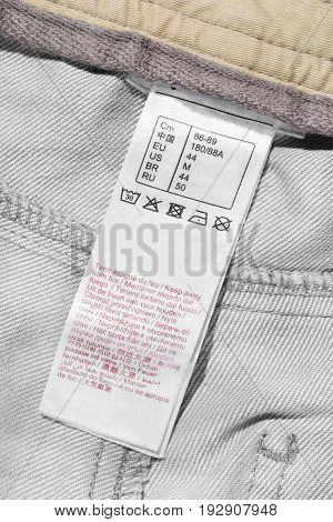 Washing instructions and size scale clothes label closeup