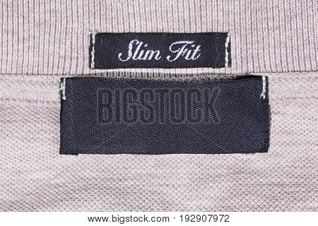 Clothes label lettered slim fit on pink knitwear as a background