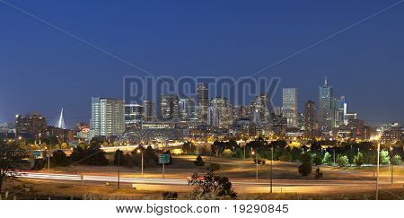 Denver skyline at night. Summer 2010. Focus on skyscrapers. Automobile traffic lights in foreground