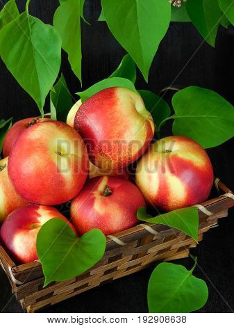 Nectarines in a wicker basket on a dark background