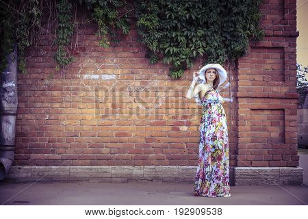 Pregnant woman on the background of an old house
