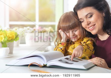 Mother reading  with her daughter  at home