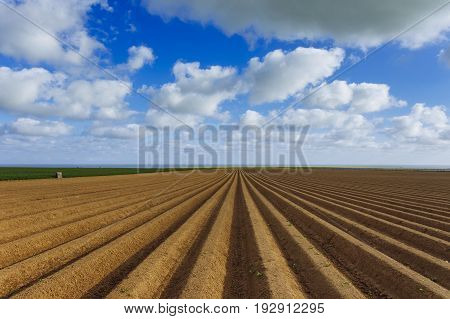 Plowed Agricultural Fields Prepared For Planting Crops In Normandy, France. Countryside Landscape, F