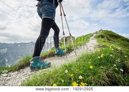 Woman running on narrow alpine mountain trail with hiking sticks.