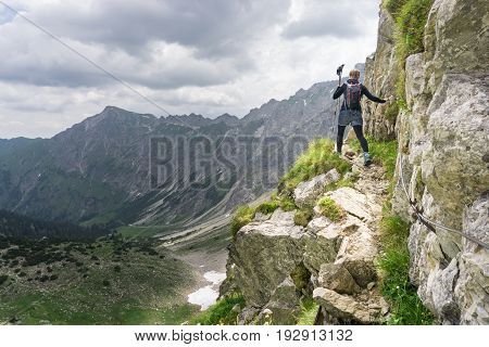 Woman walks on dangerous fixed rope trail in alpine mouintains. Very exposed, great view. Hiking and climbing in the mountains.