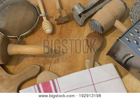 Rural kitchen utensils on vintage planked wood table from above - rustic background with free text space and with dish towel.