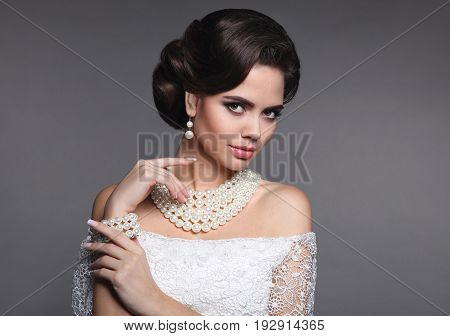 Fashion jewelry. Elegant fashionable woman portrait. Retro hair style. Beauty bride makeup. Brunette model with pearls jewelry women set present isolated on grey studio background.