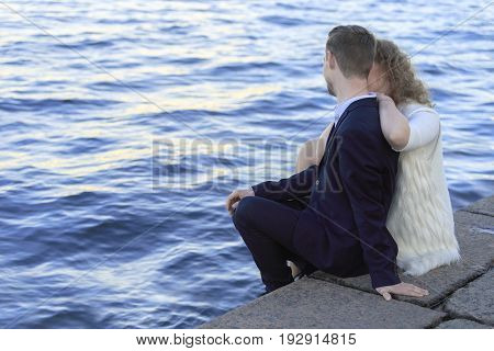 Young couple sitting on the waterfront (Saint Petersburg, Russia)