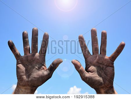 Male hands smeared with mud and raised up against the blue sky and sun