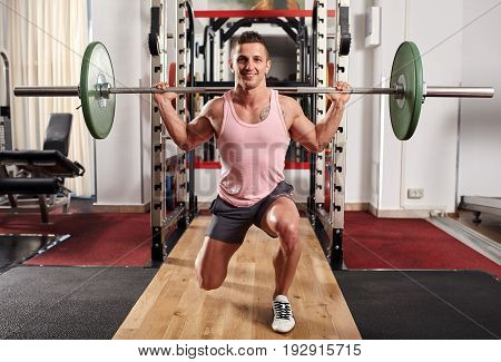 Man doing lunges with heavy barbell in the gym