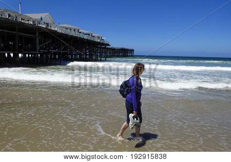 PACIFIC BEACH, CALIFORNIA ,JUNE 12. Pacific Beach on June 12, 2017 in San Diego, California. A Woman Watches Surfers as She Walks Pacific Beach in San Diego, California