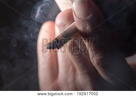 Cigarette smokes in hand on a black background
