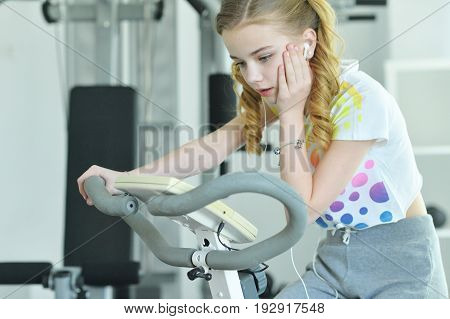 Surprised little girl sitting on treadmill with hand on her cheek
