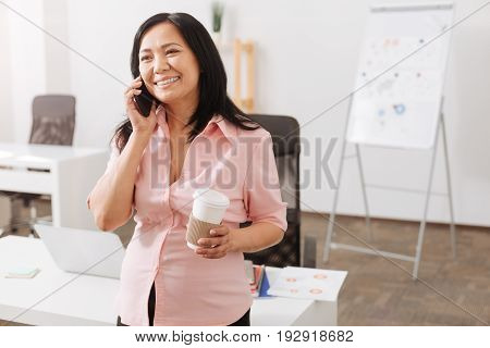 Glad to hear you. Cheerful pregnant asian woman talking on smart phone and drinking coffee while standing in the office