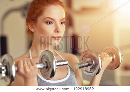 Portrait of a sporty young woman training in gym