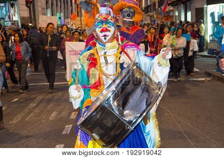 QUITO, ECUADOR- MAY 06, 2017: Unidentified man wearing clown clothes holding a big drum during a protest with the slogan alive we want them, protest against the femicide in Quito Ecuador.