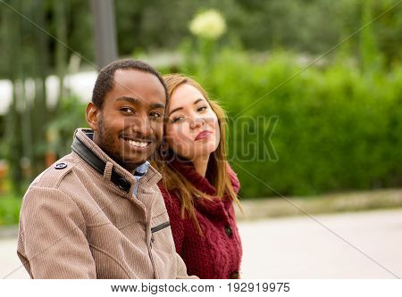 Outdoor portrait of romantic and happy interracial young couple in park.