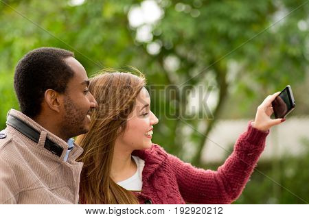 Beautiful and smiling happy interracial young couple in parl taking a selfie.