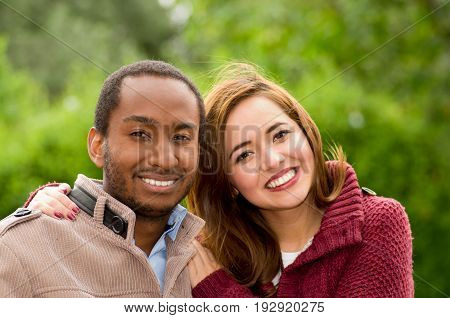Beautiful and smiling happy interracial young couple looking at camera in park in outdoors.
