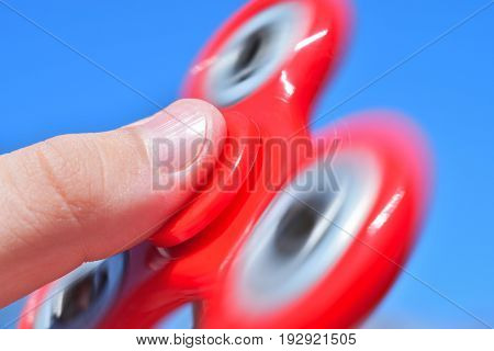 The boy is holding a spinning red spinner against the blue sky. Close-up.