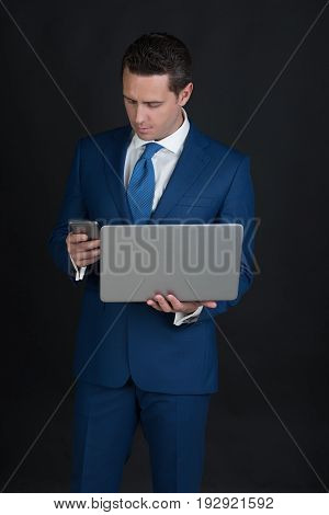 Businessman Using Mobile Phone While Working On Laptop