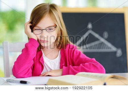 Stressed And Tired Schoolgirl Studying With A Pile Of Books On Her Desk