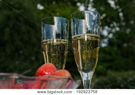 Two glasses with champagne outdoors and a blurred bowl with strawberries in the foreground