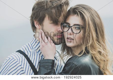 couple in love. girl or woman in stylish glasses with fashion makeup and long hair touching face of handsome unshaven man with beard. Young couple of lovers on natural background. Love and tenderness