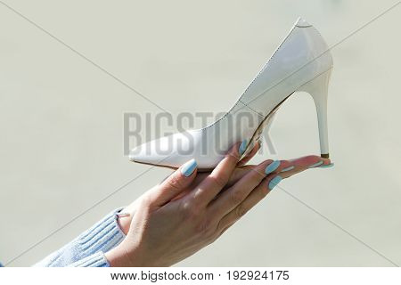 shoe white color leather on female hand on blurred background fashion and beauty shopping and presentation cinderella copy space poster