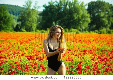 woman or happy smiling girl with long curly hair in black bodysuit in flower field of red poppy seed with green stem on natural background summer spring drug and love intoxication opium