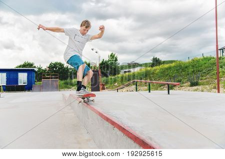 The boy skating catches the balance in the manual and slides on the railing