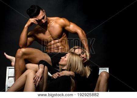 love relations of man with muscular wet athletic body and strong torso with sexy blonde twin girls in underwear pants and bodysuit on black background lesbian and gay homosexual seduction and foreplay