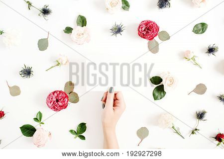 Girl's hands holding paper blank on floral frame with red and beige rose flower buds on white background. Top view flat lay decorated concept.
