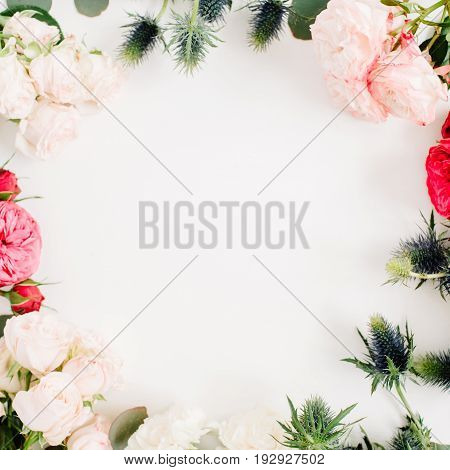 Round frame wreath made of red and beige rose flowers eringium flower eucalyptus branches and leaves on white background. Flat lay top view. Floral background
