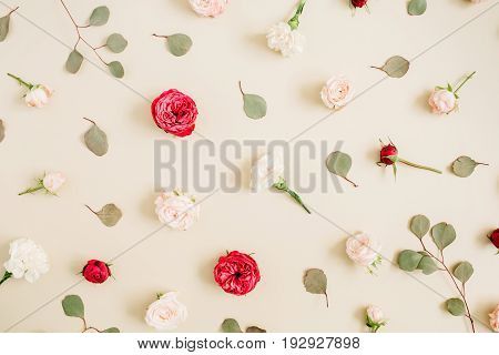 Flowers pattern texture made of beige and red roses eucalyptus leaf on pale pastel beige background. Flat lay top view. Floral texture background.