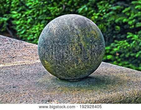 Stone ball with surface pores set on a pedestal. Green background