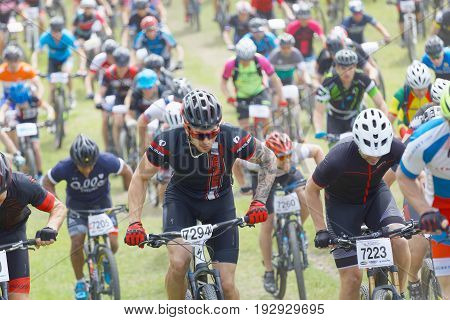 STOCKHOLM SWEDEN - JUNE 11 2017: Lots of mountain bike cyclist struggling in a steep uphill at Lida Loop Mountain bike Race. June 11 2017 in Stockholm Sweden