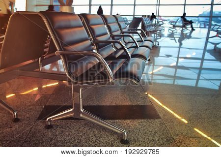 Passengers are waiting for a flight to plane at the airport. Seats in an airport lounge on a background of silhouettes of passengers