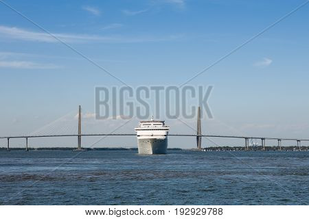 Head-on view of a cruise ship in front of the Ravenel Bridge in Charleston SC. Recognizable smoke stacks and markings have been removed from the ship. Plenty of copy space in sky if needed.