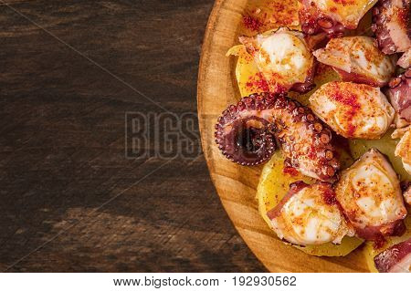 A closeup photo of pulpo a la gallega, an octopus with boiled potatoes, typical Spanish Galician dish, on a traditional wooden plate, with copy space