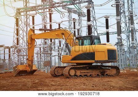 Excavator on industrial construction of energy facility. Excavator on background of industrial electrical equipment of power plant. Construction machinery and heavy machinery