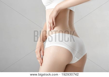 woman's ass in white lingerie on the grey background