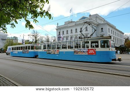 GOTHENBURG SWEDEN - MAY 2017: Blue old electric train running in Gothenburg Sweden. Building on a background is Stora Teatern -Gothenburg's scene for Swedish and international performances.
