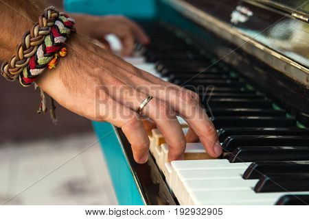 The Hands Of A Young Man Playing Piano On A Street Of City.