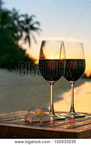 Two glasses of red wine at sunset on beach