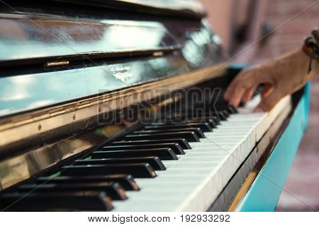 A Hand Of A Young Man Playing Piano On A Street Of City, Closeup.