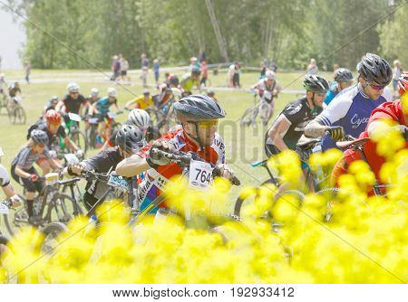STOCKHOLM SWEDEN - JUNE 11 2017: Group of men and woman leading his mountain bike uphill competitors behind at Lida Loop Mountain bike Race audience in background. June 11 2017 in Stockholm Sweden