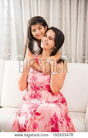 playful happy Indian little girl covering her mother's eyes and giving her surprise while sitting on white sofa in drawing room