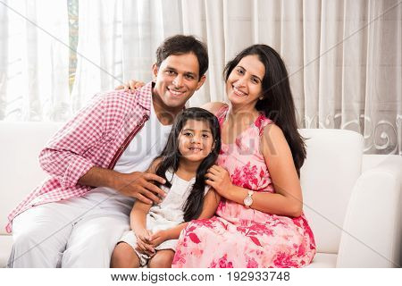 Family time - Candid Portrait of smart indian family of three while sitting on sofa. Indian or asian family group photo. Cute girl child sitting between mother and father on sofa for portrait photo